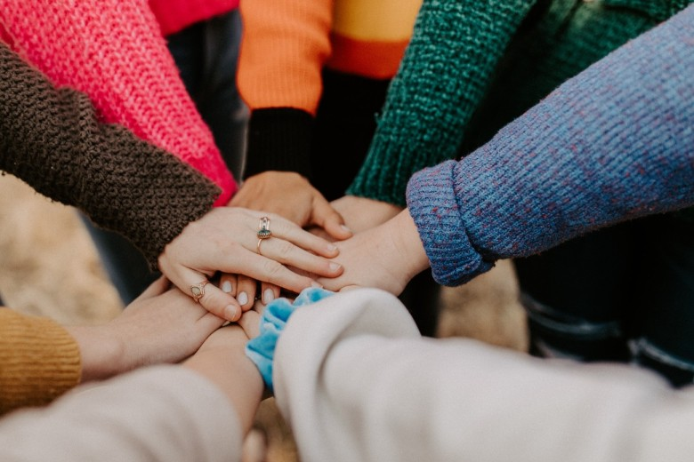 how to handle workplace conflict - team of people with their hands together showing teamwork colorful sweaters
