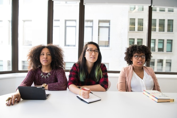how to handle workplace conflict - three young women at work sitting at confrence table