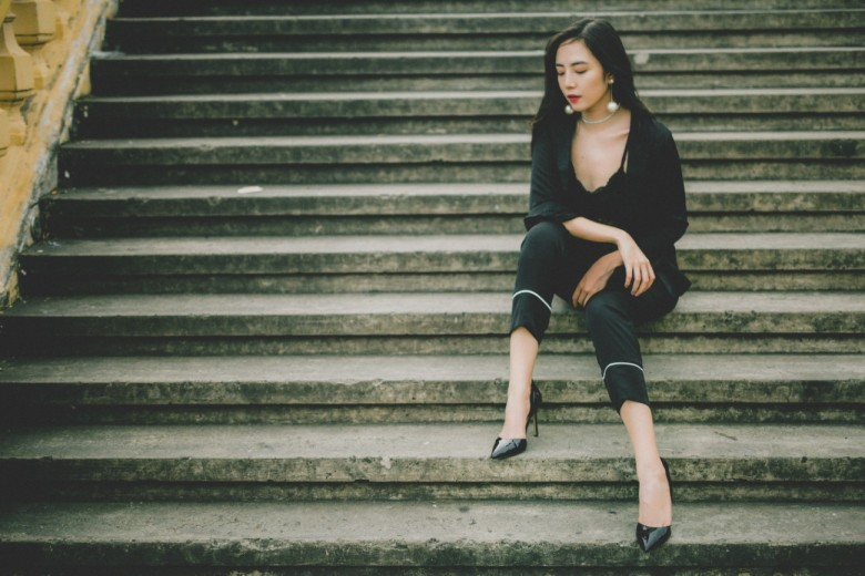 how to handle workplace conflict - woman in dress clothes sitting on stairs looking down