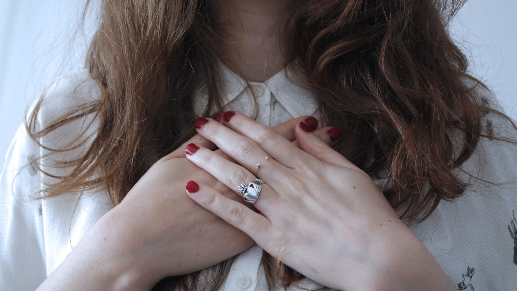 woman holding hands over chest with red painted fingernails - how to practice self compassion in a breakup