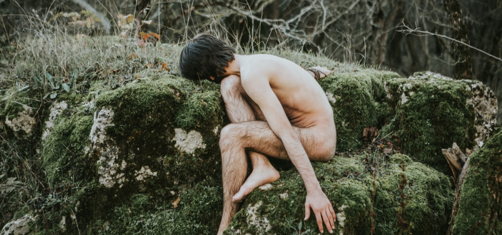 man naked sitting on mossy rock self compassion in a breakup