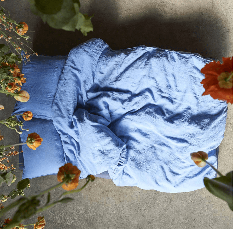 blue bed sheets with flowers around the bed